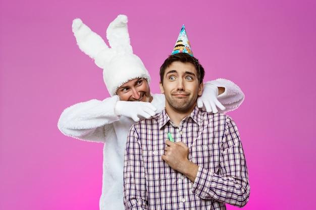 Kaninchen erschreckender betrunkener mann über lila wand. geburtstagsfeier.
