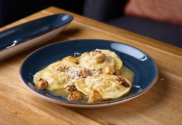 Kaninchenravioli mit pilzsauce und raps-parmesan