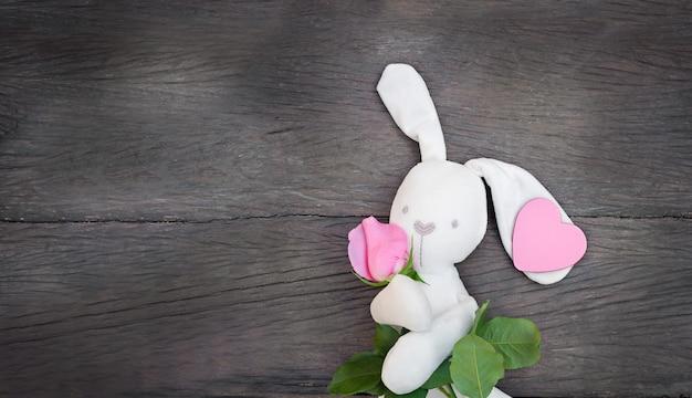 Kaninchenspielzeug mit blume und herz auf einem hölzernen hintergrund. weißer hase, der rosa rose und herzkopierraum hält