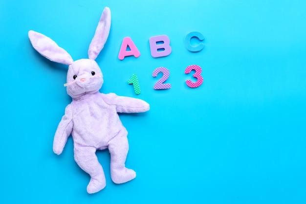 Kaninchenspielzeug mit englischem alphabet-puzzle und ziffern auf weiß. bildungskonzept, kopierraum