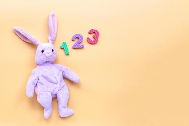 Kaninchenspielzeug mit ziffern auf gelbem hintergrund. bildungskonzept.