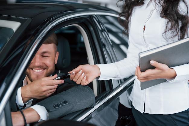 Kann nicht mit emotionen umgehen. glücklicher besitzer des neuen autos, das innen sitzt und schlüssel von weiblichem manager nimmt