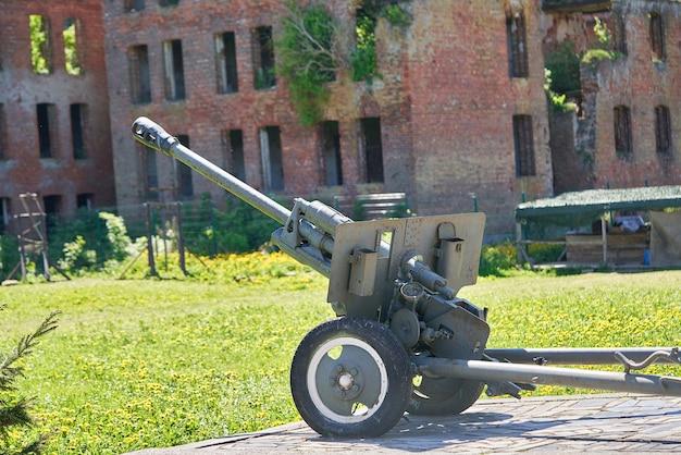 Kanone zweiter weltkrieg vor dem hintergrund eines zerstörten roten backsteingebäudes