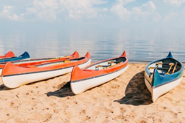 Kanu auf strand am sonnigen sommertag auf unscharfem meer mit wolken