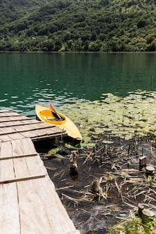 Kanu, das nahe dem hölzernen pier auf see schwimmt