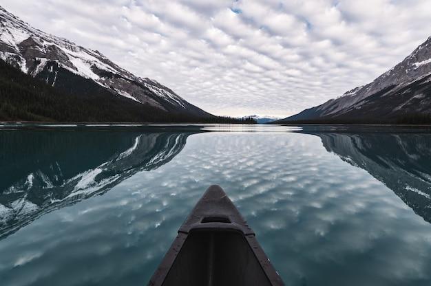 Kanufahren mit bewölkter reflexion auf maligne see in den rocky mountains am jasper-nationalpark, kanada