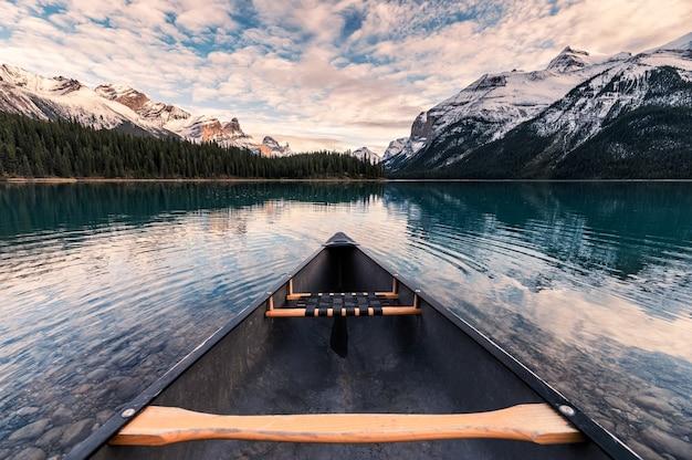 Kanufahren mit kanadischen rocky mountains in spirit island am maligne lake im jasper national park, kanada
