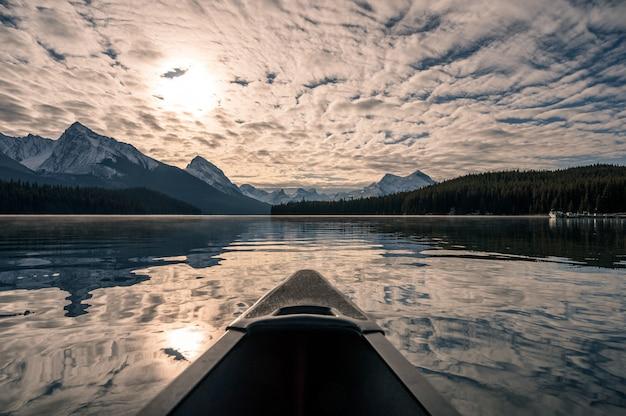 Kanufahren mit kanadischen rocky mountains und bewölktem sonnenlicht auf dem maligne-see im jasper-nationalpark