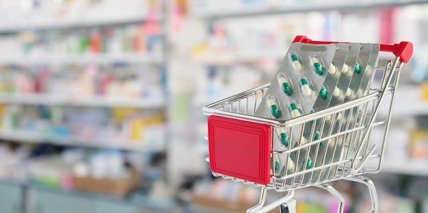 Kapsel im einkaufswagen mit unscharfem hintergrund der apotheke