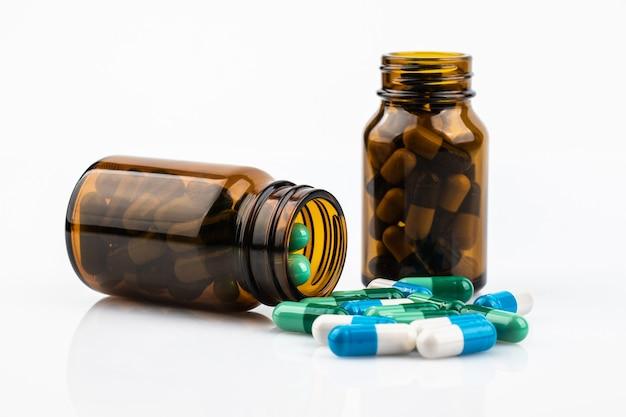 Kapselmedizin verschüttet in der flasche lokalisiert auf weißem hintergrund Premium Fotos
