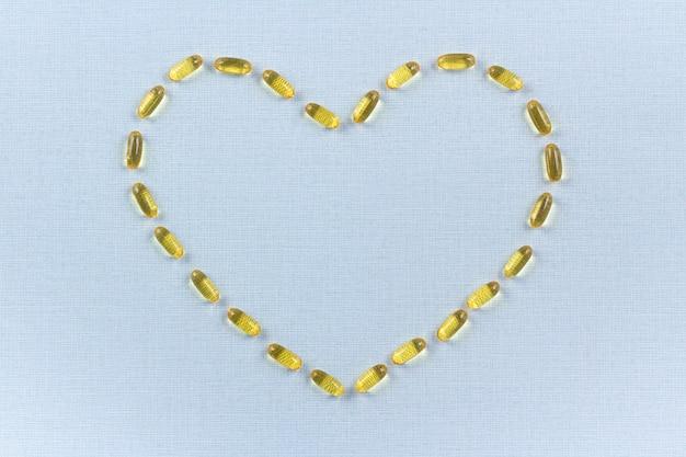Kapseln omega 3 in form eines herzens auf blauem hintergrund. gesundheitswesenkonzept, flache lage, kopienraum.