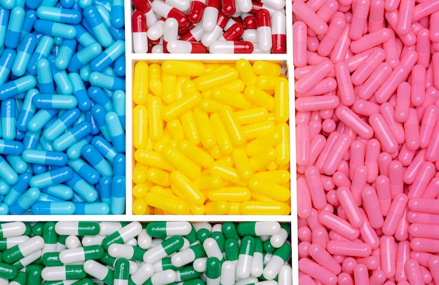 Kapselpillen in plastikschale. vitamine und ergänzungen konzept. auswahl von antibiotika. herstellung von pillenkapseln. drogenkonsum in der dermatologischen klinik. ergänzungsindustrie. pharmaindustrie.