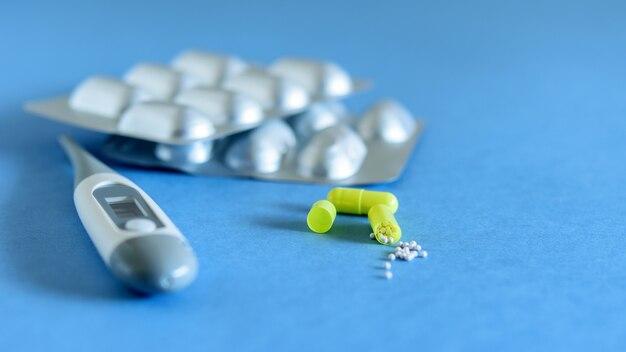 Kapseltabletten und thermometer auf der blauen hintergrundnahaufnahme. gesundheitswesen, medizin gegen das virus und die grippe.