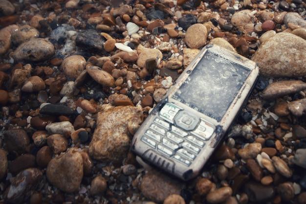 Kaputtes und ertrunkenes telefon auf steinen im meer
