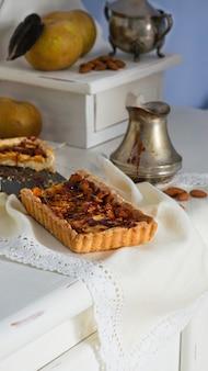 Karamell-apfelkuchen auf dem weißen hölzernen buffet, graue labäpfel