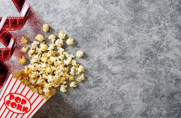 Karamell-popcorn in einem pappbecher auf einem loft-hintergrund 35-mm-film flachgelegtes kino