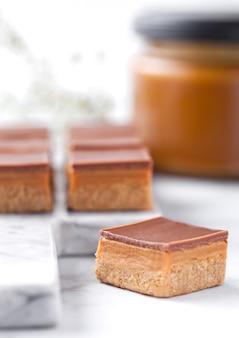 Karamell- und kekskuchen beißt nachtisch auf marmorbrett mit glas gesalzenem karamell