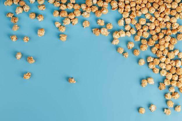 Karamellpopcorn durch eine welligkeit auf einem blauen hintergrund, in der form eines rahmens. köstlicher fang für filme, serien, cartoons. frei rechtmäßig, verbrechen. minimalistische konzession.