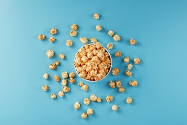 Karamellpopcorn in einer weißen glasschale mit einer schere auf einer blauen oberfläche. ein köstlicher fang zum filmen von filmen, fernsehserien und cartoons. freie legale verbrechen.