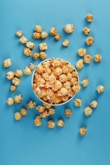 Karamellpopcorn in einer weißen glasschale mit schere auf einem blauen hintergrund. ein köstlicher fang zum filmen von filmen, fernsehserien und cartoons. freie legale verbrechen.