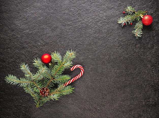 Karamellstock mit ästen stößt perlen und weihnachtsbaumspielzeug auf dunklem hintergrund