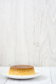 Karamellvanillepudding und -eier auf weißem holztischkopienraum
