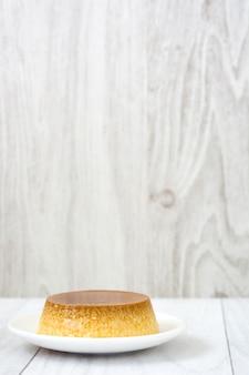 Karamellvanillepuddingnachtisch auf weißem teller mit holzoberfläche.
