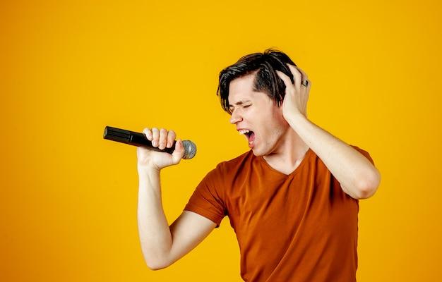 Karaoke-mann singt ein lied in ein mikrofon, auf einem gelben hintergrund. ein lustiger mann hält ein mikrofon in der hand, während der karaoke-sänger ein lied singt! drehzapfen auf gelbem grund