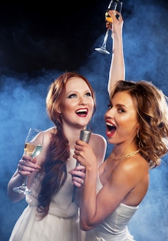 Karaoke-party. schönheitsmädchen mit einem mikrofon, das auf dunklem hintergrund singt und tanzt.