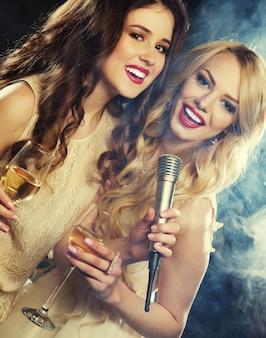 Karaoke-party. schönheitsmädchen mit einem mikrofon, das über dunklem hintergrund singt und tanzt.
