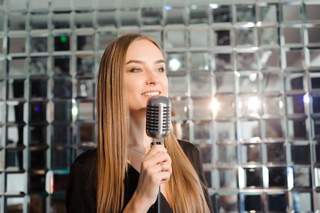 Karaoke-party. schönheitsmädchen mit einem mikrofongesang.