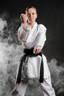 Karate frau, die vorderansicht aufwirft