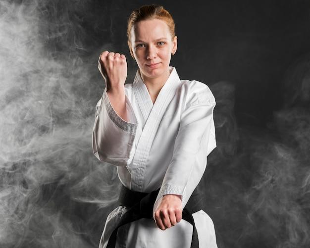 Karate-kämpfer, der mittleren schuss aufwirft