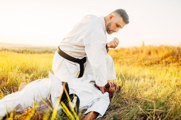 Karate-kämpfer gibt dem gegner einen entscheidenden tritt und trainiert den kampf im sommerfeld. kampfkunstkämpfer beim training im freien, technikpraxis