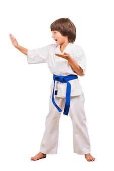 Karate kid. in voller länge des kleinen jungen in karate-pose. position der karate-choreographie.