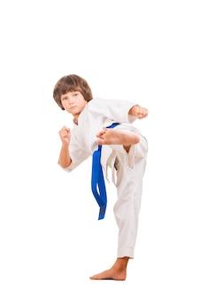 Karate kid. kleiner junge, der kampfsportbewegungen macht, während er auf weißem hintergrund isoliert ist