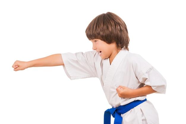 Karate kid. seitenansicht eines kleinen jungen, der kampfsportbewegungen macht, während er auf weißem hintergrund isoliert ist