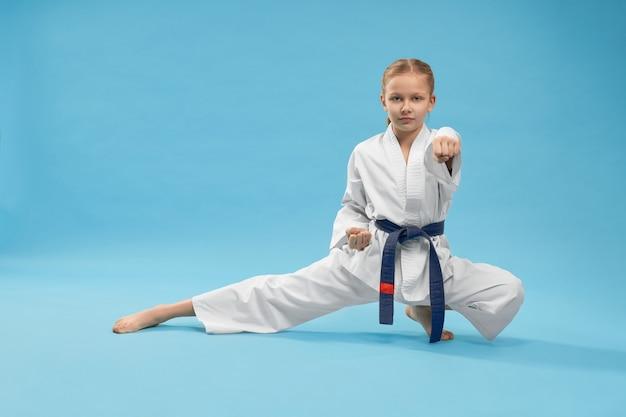 Karate-mädchen, das in haltung steht und schlag schlägt.