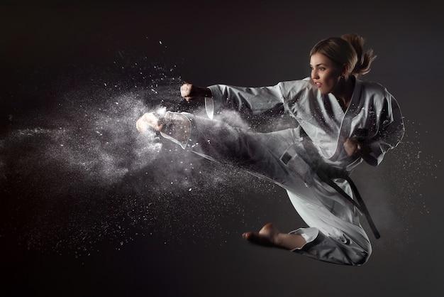 Karate-mädchen hüpft und tritt