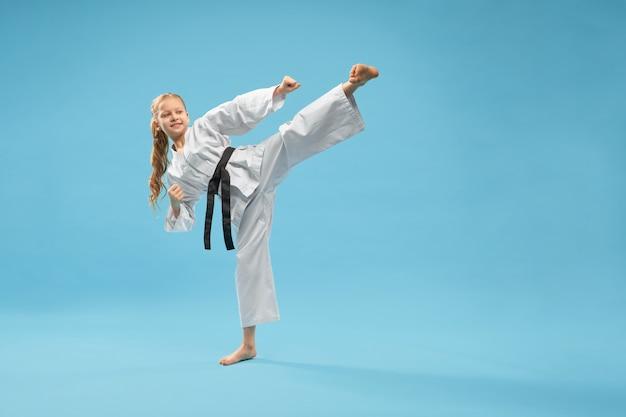 Karate-mädchen im weißen kimono, der kampfkunst praktiziert.