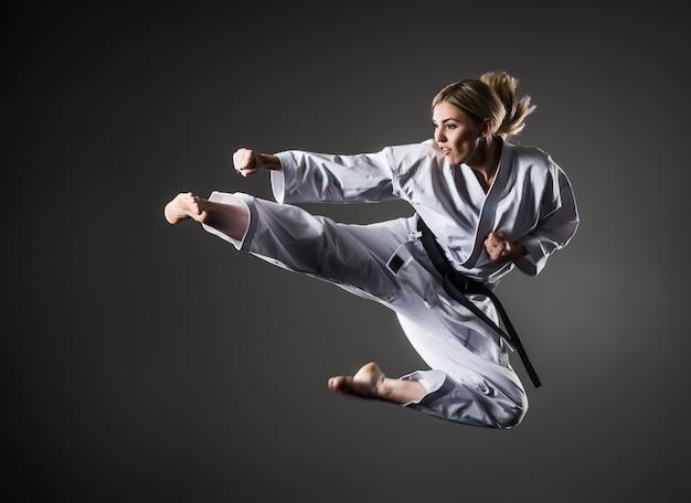 Karate-mädchen im weißen kimono mit schwarzem gürtel im sprung