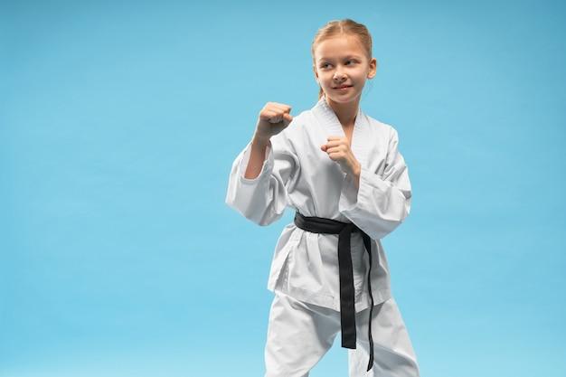 Karate-mädchen in verteidigungsposition, kampfsport praktizierend.