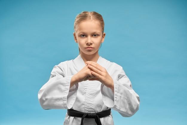 Karate-mädchen mit dem schwarzen gürtel, der händeposition übt.