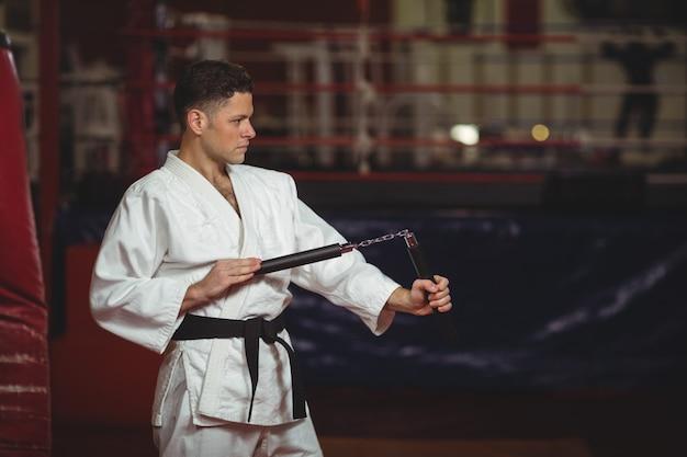 Karate-spieler, der mit nunchaku übt