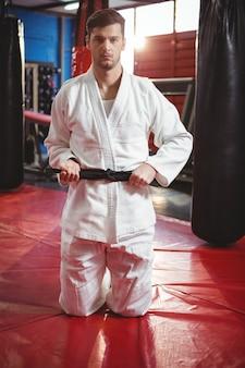 Karate-spieler, der seinen gürtel bindet