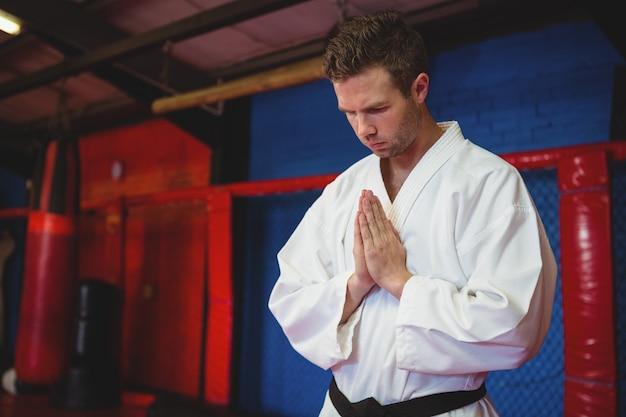 Karate-spieler in gebetshaltung