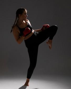 Karatefrau, die einen tritt und einen dunklen hintergrund gibt