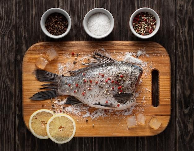 Karausche zum backen mit pfeffer, salz und zitronen auf holzküchenbrett vorbereitet.