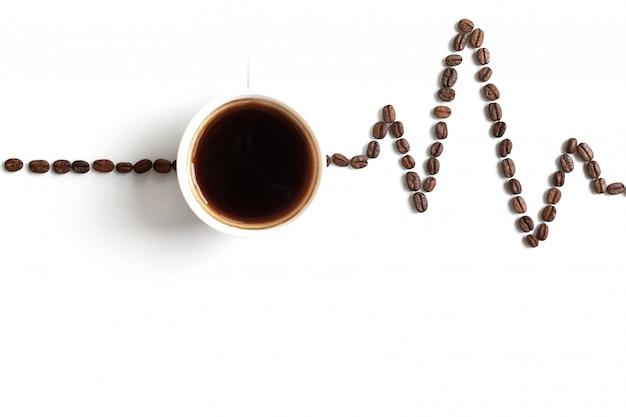 Kardiogramm gemalt mit kaffeebohnen und tasse kaffee. das konzept der wirkung von koffein auf das herz.