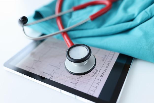 Kardiogrammergebnisse und stethoskop auf tablette. untersuchung des herz-kreislauf-systems